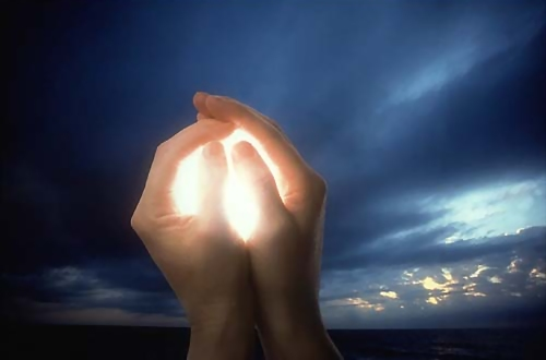 hands holding a glowing ball of light