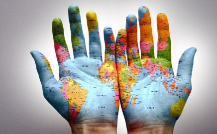 map of the world overlaid on two open palm hands